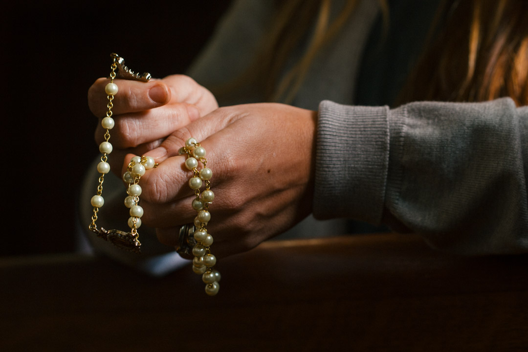 A woman kneels in a pew and prays the rosary
