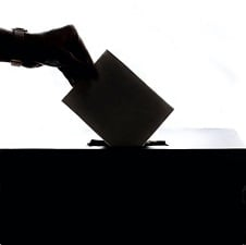 A silhouette of a woman's hand casting a ballot