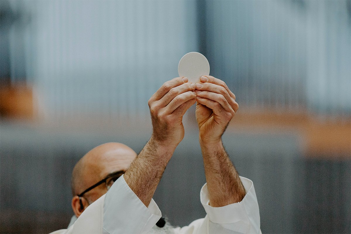 A priest lifts the Communion high