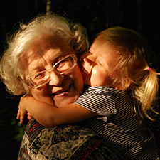 Grandmother being hugged joyfully by a granddaughter