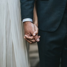 Focused on the hands of a bride and groom on their wedding day. They're holding hands