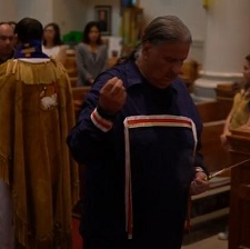 An elder performs a smudge ceremony with a priest behind him