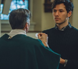 A man receives the Eucharist from a priest