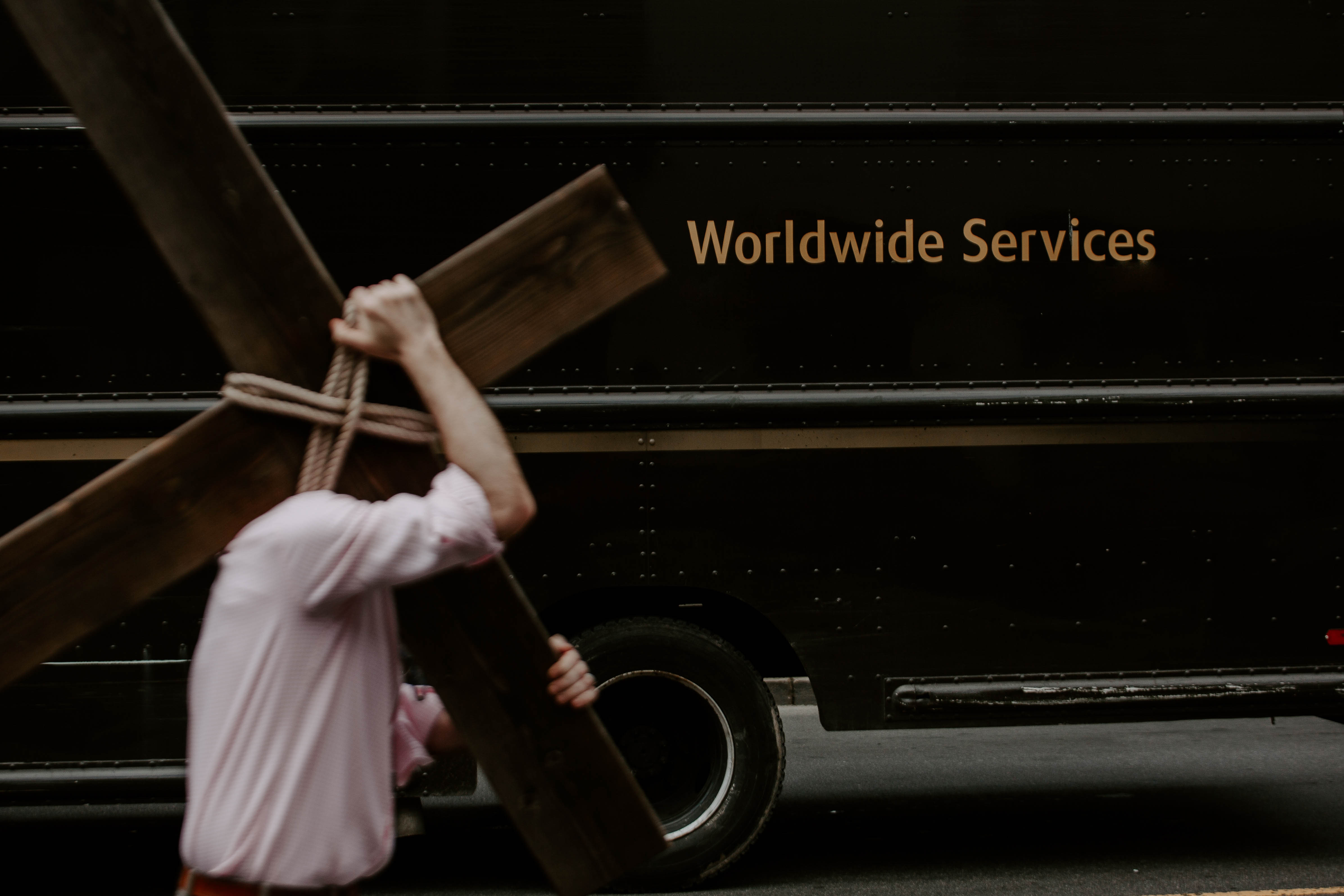 A man carries a cross in a modern city's downtown core