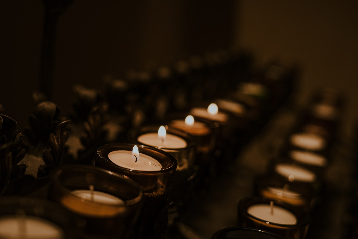 A side angle on lit votive candles in a church