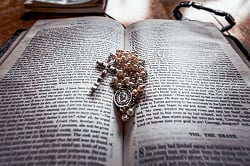 A Bible opened on a table with a rosary laying on top of it