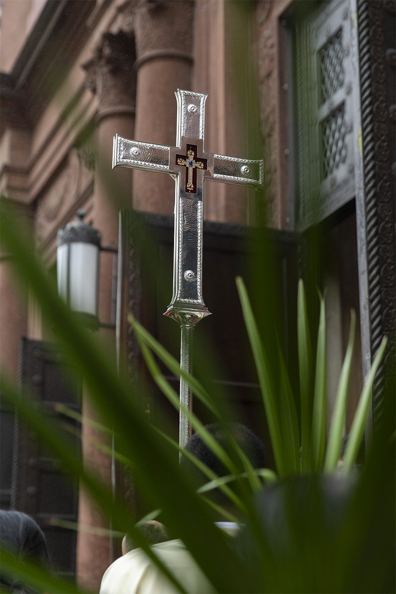 A cross with palm leaves in the foreground