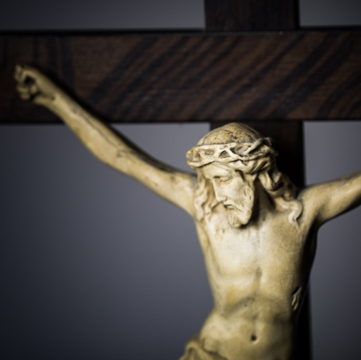 A close -up of Jesus on a crucifix with a grey background