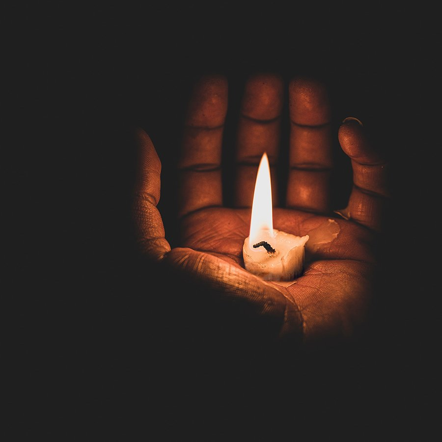 Open hand with a lit candle