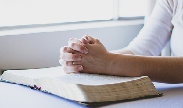 Praying hands with open book