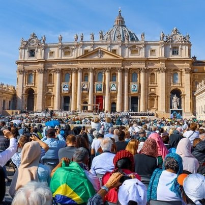 A crowd of people from around the world sit outside of St. Peter's Basilica in the Vatican