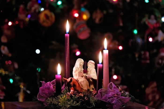 Four Advent candles at home with figurines