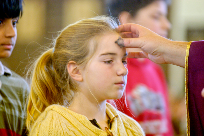 Girl receiving ashes on Ash Wednesday