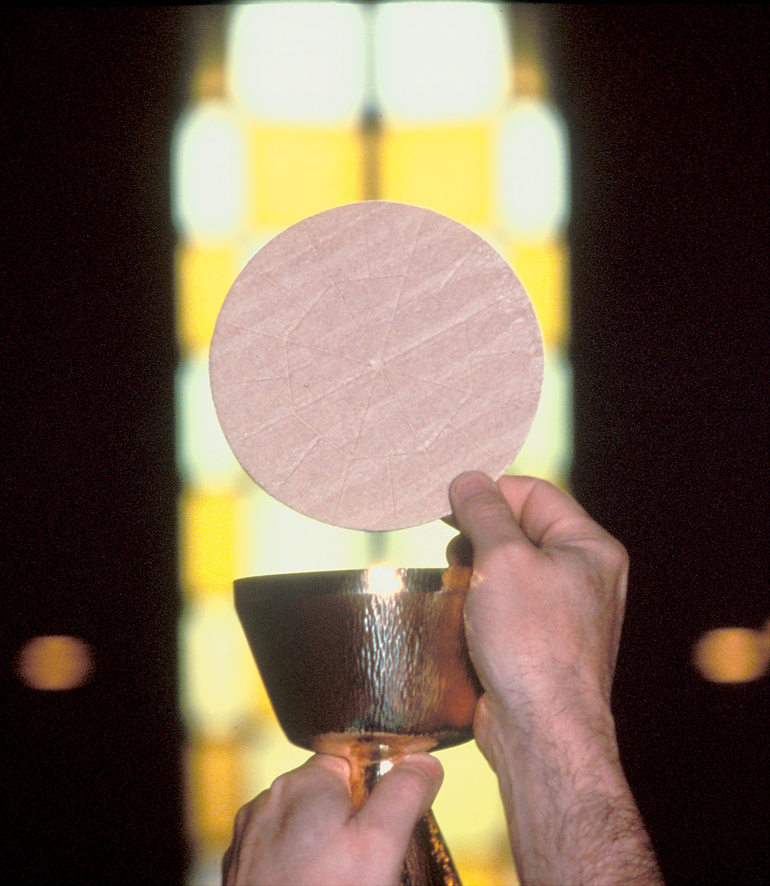 The Eucharist being held up by a priest in front of a stained glass window