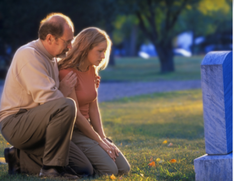 Two people next to a grave picture