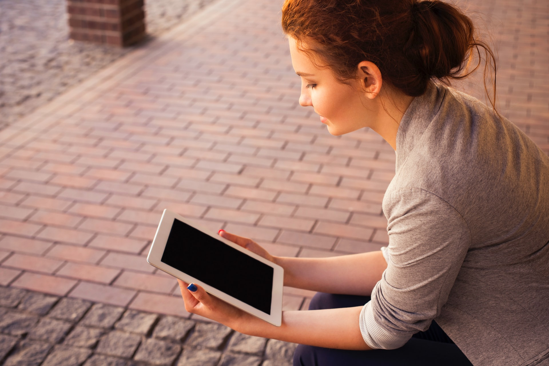 A woman read a tablet device on a sunny day