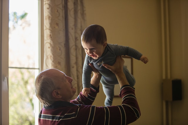 A grandfather holds a baby over his head like it's an airplane