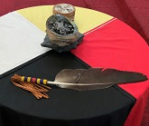 A table with the four directions cloth and smudging materials on top