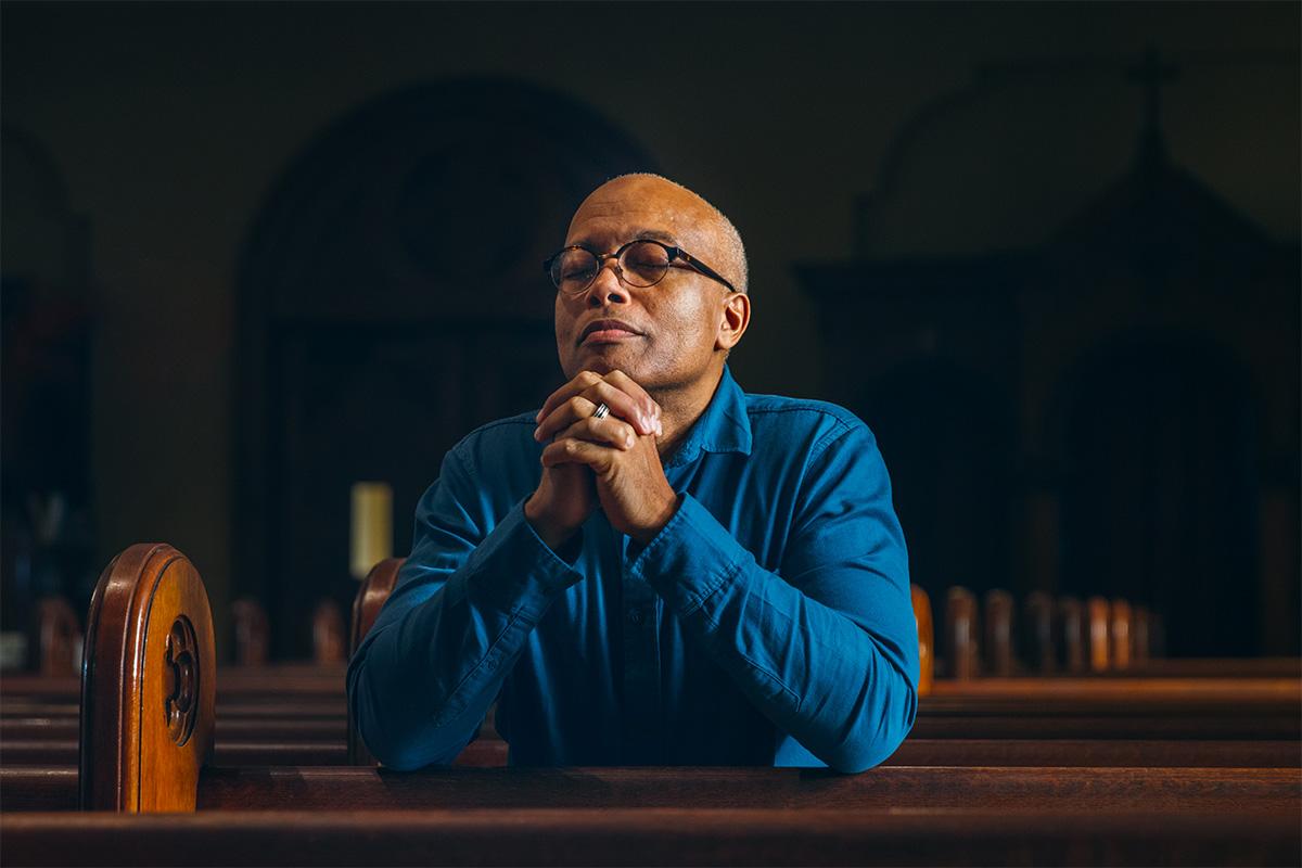 Man kneels in a church smiling as he prays