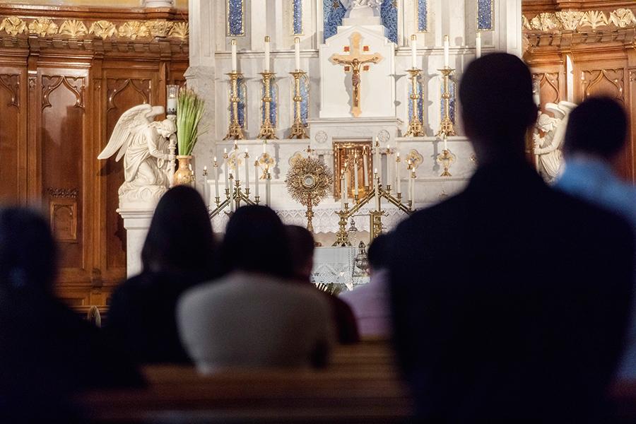 Group of people praying at church during adoration