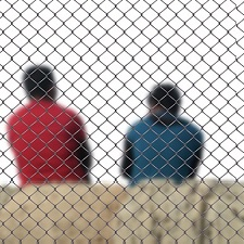 Two men sitting with their backs turned behind a chain-link fence