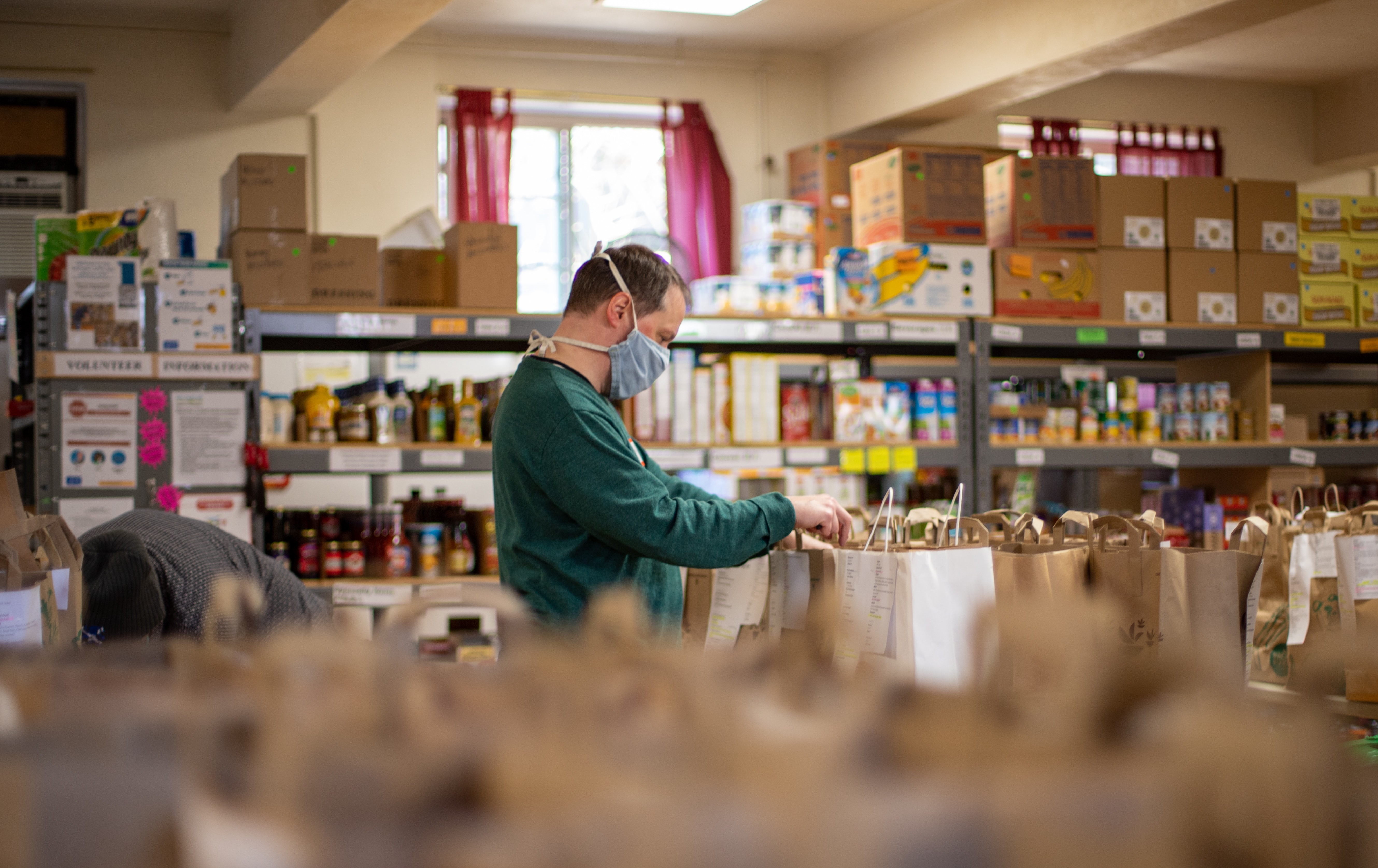 A person wearing a mask fills bags in a food bank