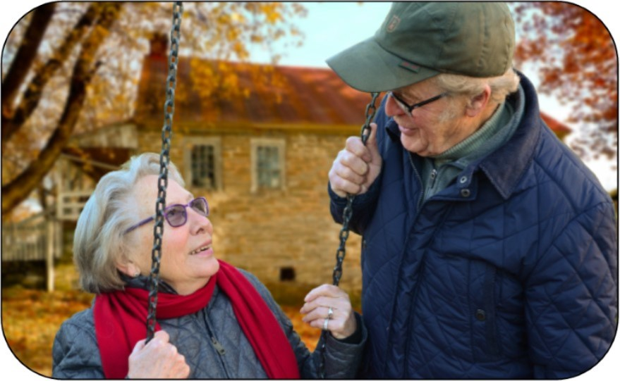 elderly couple, woman is on a swing, husband next to her and they are smiling at each other