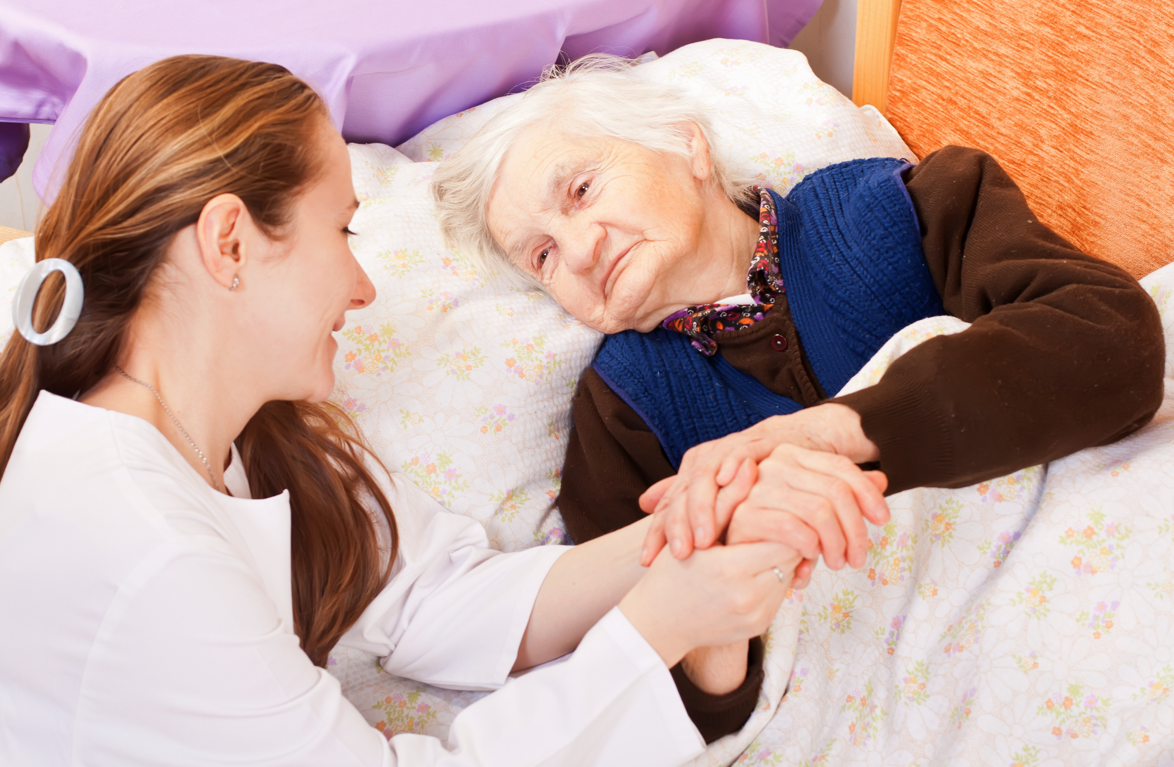 image of woman sitting next to bed with elderly sick woman, they are smiling and holding hands