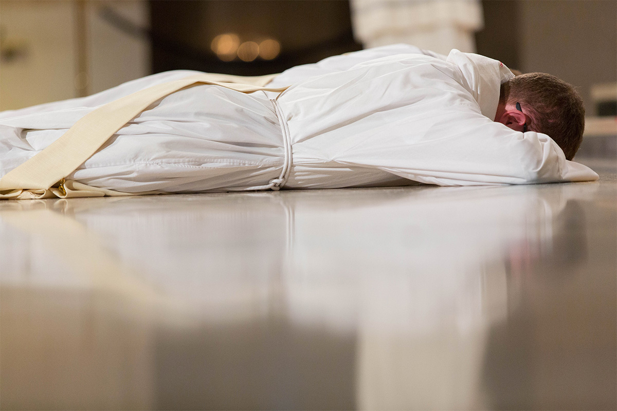 A priest lays on the ground during Holy Orders