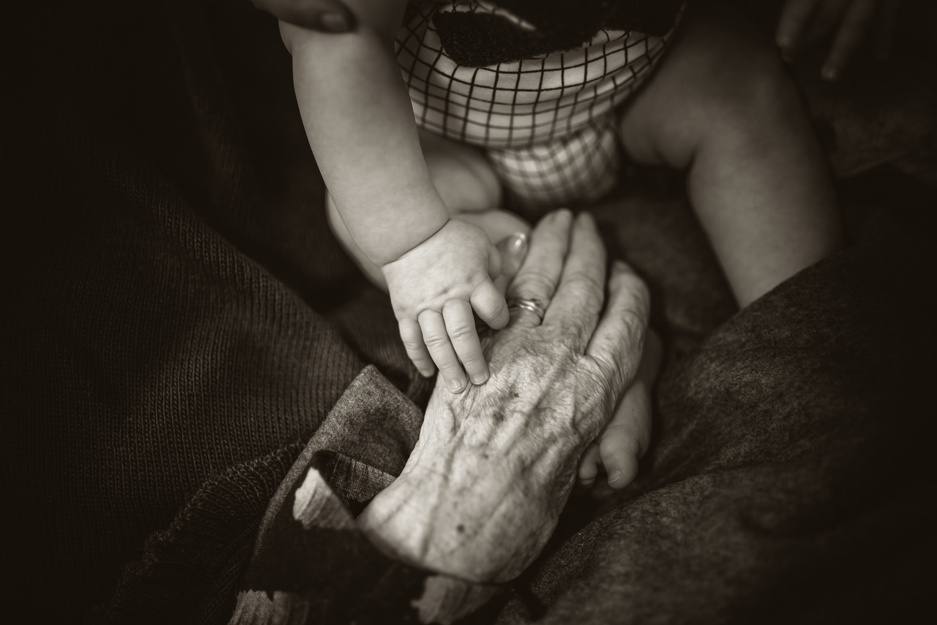 An elderly person holds hands with a baby in a black and white photo
