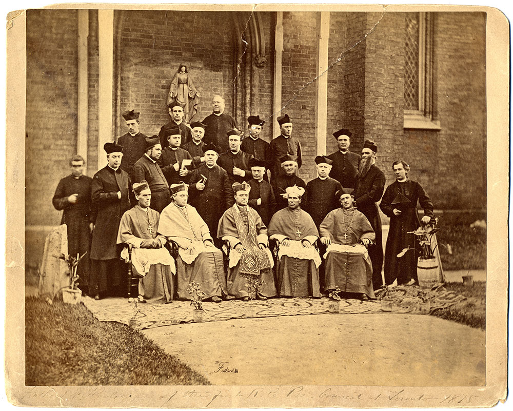 Black-and-white group of bishops and priests in episcopal dress in front of St. Michael's Cathedral.