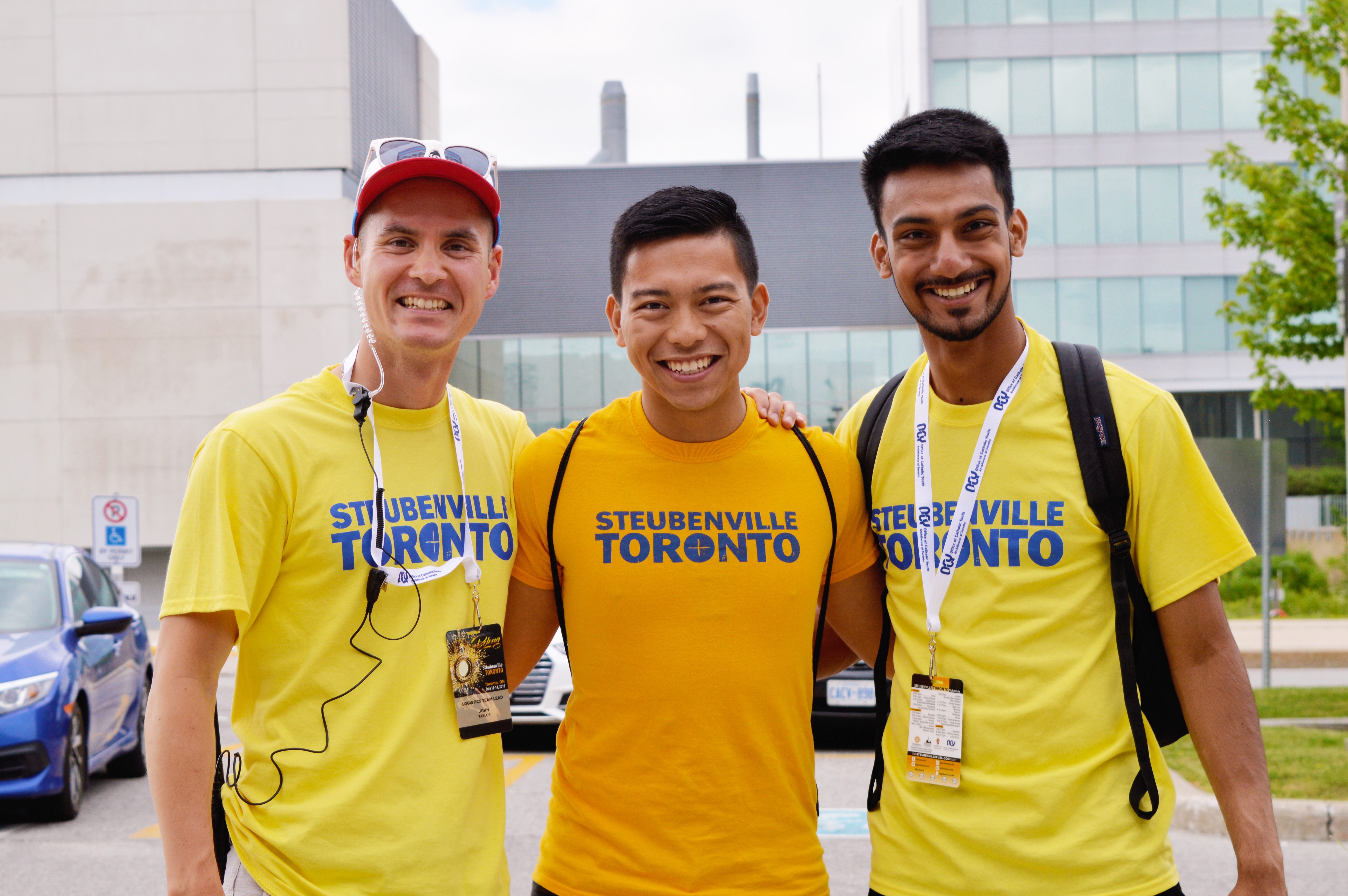 Three men of various ethnicities wearing yellow shirts and smiling together